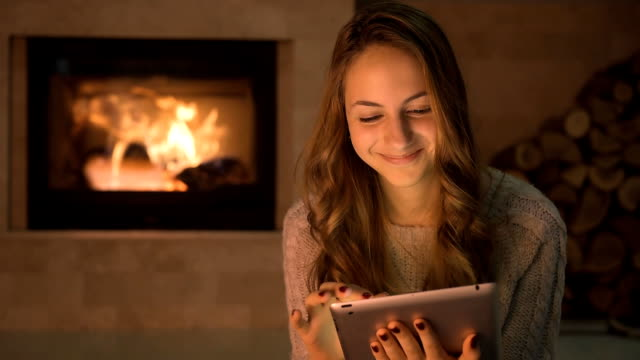 Cinemagraph - Young woman with her dog sitting on floor and using tablet . Cinemagraph - Young woman with her dog sitting on floor and using tablet . Motion Photo. fireplace stock videos & royalty-free footage