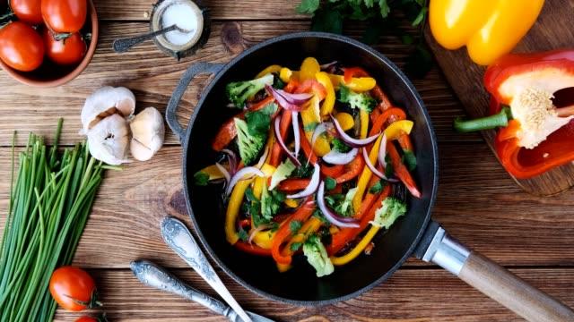 cinemagraph-matlagning grönsaker stek panna. uppifrån. rörelse foto. - frying pan bildbanksvideor och videomaterial från bakom kulisserna