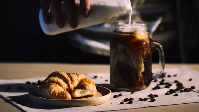 cinemagraphs : cup of cappuccino cafe and croissant on table - coffee stock videos & royalty-free footage