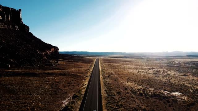 sinematik hava drone ile büyük kayalık dağ ve araçların abd'de karayolu üzerinde nefes kesen çöl vahşi bir kadeh. - bakir yer stok videoları ve detay görüntü çekimi