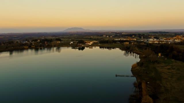vídeos de stock, filmes e b-roll de tiro aéreo cinematográfico do lago com rua e carros moventes no fundo - sol nascente horizonte drone cidade