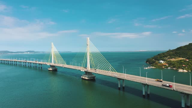 Cinematic aerial shot ofAnita Garibaldi bridge above the turquoise color brazilian ocean located in Laguna, Santa Catarina, Brazil suspension bridge stock videos & royalty-free footage