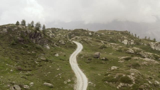 dağda sinematik hava görünümü çakıl iz yol. bulutlu, sis ve pus. i̇leri dolly - bakir yer stok videoları ve detay görüntü çekimi