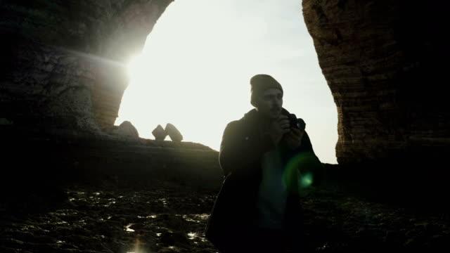Cinematic back lit shot of male photographer taking photos of rocky Normandy sunny sea beach near Etretat slow motion.