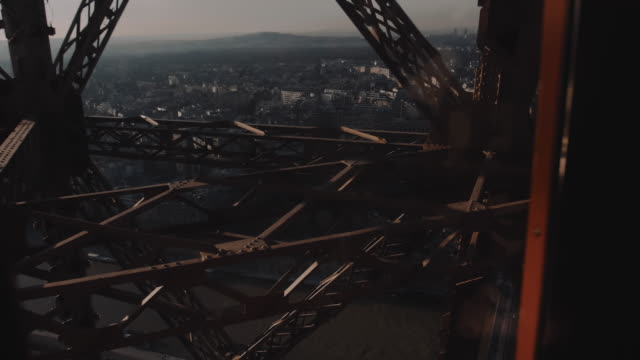 Cinematic background shot, camera is inside glass elevator moving up inside Paris Eiffel Tower steel structure bars.