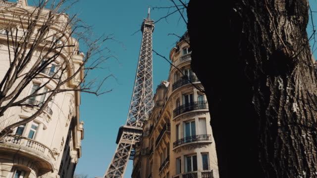 vidéos et rushes de caméra cinématographique se déplace à gauche le long des arbres, de vieux blocs d'appartements révélant épique tour eiffel dans le soleil du matin d'automne paris. - paris