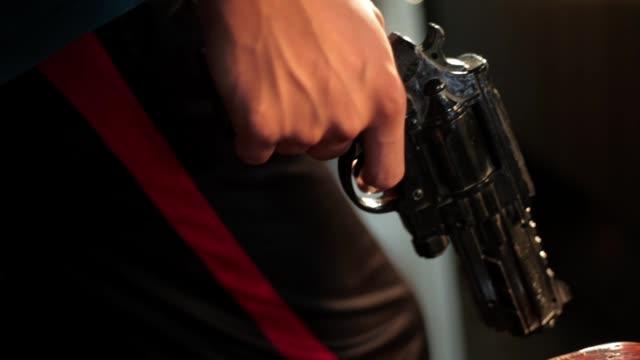 vidéos et rushes de film de dolly cinématographique d'une main humaine retenant le pistolet noir de revolver coloré allumé avec des lumières d'or. - armement