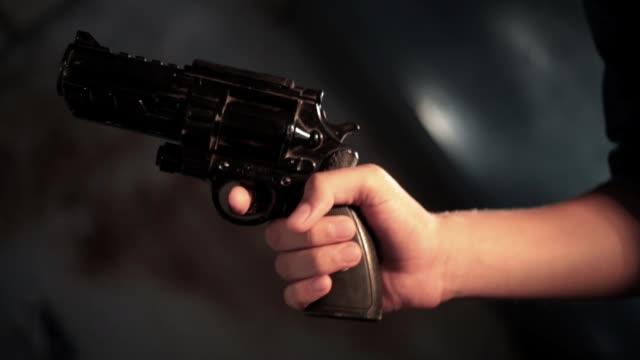 vídeos de stock e filmes b-roll de cinematic dolly shot of a human hand holding black colored revolver gun lit with golden lights. - puxar