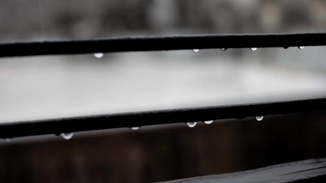 Cinematic dolly shot of a window with metallic bars and raindrops on it.