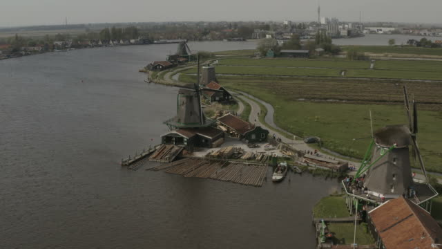 Cinematic drone view of Zaanse Schans windmills in Netherlands 4k Aerial view of windmills in Zaanse Schans village in the north of Netherlands. This video has been realized with Hight Resolution , Hight Bitrate and flat color profile. coastal feature stock videos & royalty-free footage