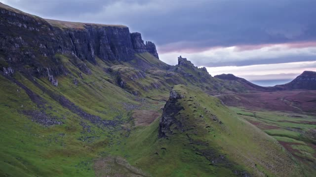 Cinematic flight over the Quiraing during sunrise on the eastern face of Meall na Suiramach, Isle of Sky