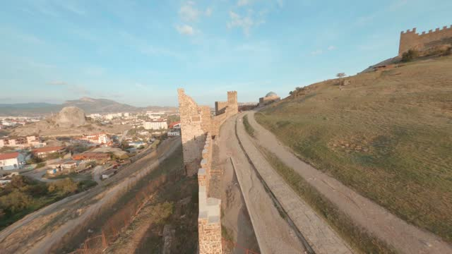Cinematic fpv drone flying over Genoese fortress area on Black Sea landscape. Ancient fortress architecture with long wall and tower on modern city and sea bay background.