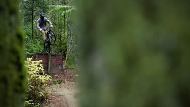 シネマティックマウンテンバイクダートジャンプは、森の木のスローモーションで囲まれています ビデオ