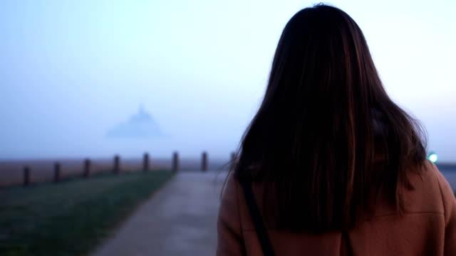 filmisk bakifrån av vackra unga turist kvinna går till mystiska dimmiga mont saint michel fästning slow motion. - endast unga kvinnor bildbanksvideor och videomaterial från bakom kulisserna