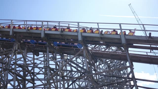 Cinematic roller coaster climbs up hill as seen from driving car