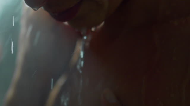Cinematic shot of a beautiful woman in the shower who washes herself in slowmotion. – film