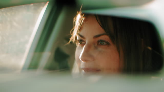 cinematic shot of a pretty woman driving during the day. - woman mirror video stock e b–roll