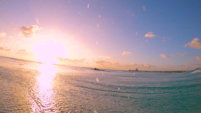 lens flare: filmische aufnahme einer röhrenwelle, die über die kamera spritzt und den sonnenuntergang filmt. - horizont über wasser stock-videos und b-roll-filmmaterial