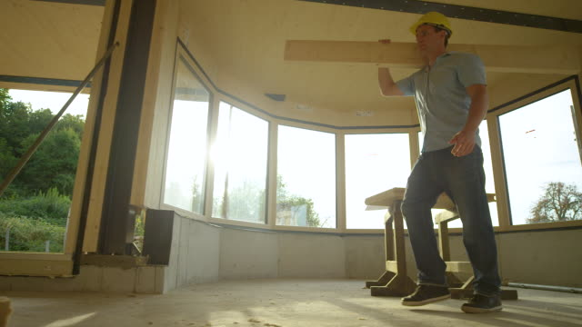 LOW ANGLE Cinematic shot of a young contractor carrying a plank across CLT house