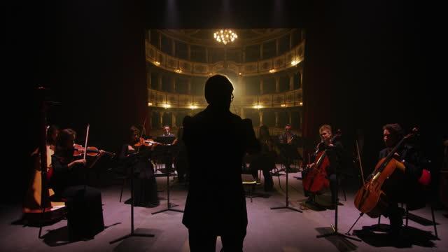 vídeos de stock e filmes b-roll de cinematic shot of conductor directing symphony orchestra with performers playing violins, cello and trumpet - atuação