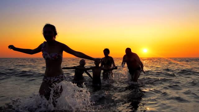 vídeos y material grabado en eventos de stock de filmada de personas familiares divirtiéndose bailando y quedando sin agua de mar contra la puesta del sol. filmada de steadicam cinematográfica - caribe
