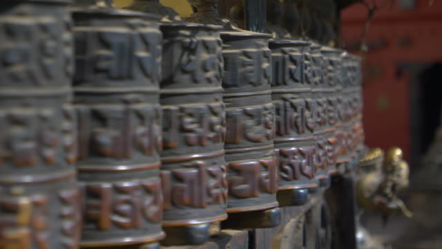 close up: cinematic shot of metal prayer wheels spinning inside a hindu temple. - мани стоковые видео и кадры b-roll