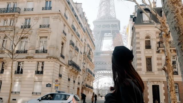 Cinematic side view, elegant woman walking along Paris street, sunny Eiffel Tower is seen between houses slow motion. video