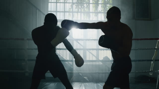 Cinematic slow motion close up shot of two professional young muscular shirtless male boxers are fighting  in a boxing ring Cinematic slow motion close up shot of two professional young muscular shirtless male boxers are fighting  in a boxing ring. action movie stock videos & royalty-free footage