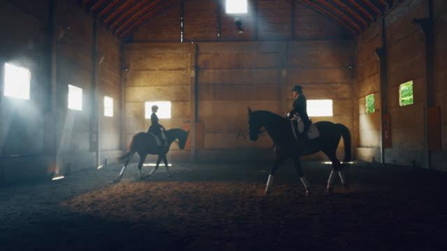 vidéos et rushes de le ralenti cinématographique des jeunes maîtres d'équitation rectifiés dans un vêtement professionnel pratiquent des exercices de couple pour la concurrence des courses de cheval et du dressage sur une salle d'équitation - dressage équestre