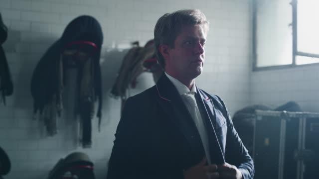 vidéos et rushes de le ralenti cinématographique du jeune maître d'équitation masculin s'habille dans un vêtement professionnel avant de commencer à pratiquer des exercices pour la concurrence des courses de cheval et du dressage sur une salle d'équitation - dressage équestre