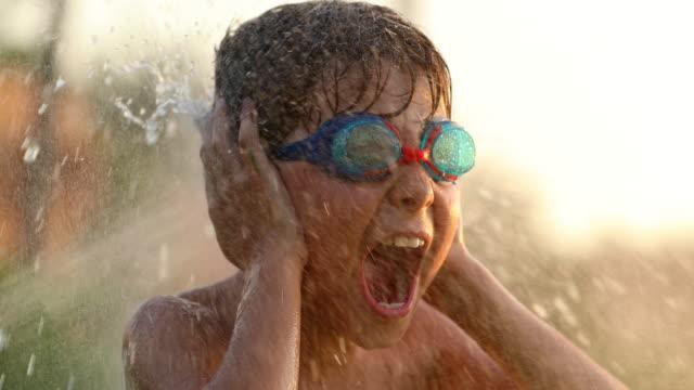 vídeos y material grabado en eventos de stock de toma cinematográfica lenta a 60fps de niño gritando con las orejas cubriendo sus manos mientras sumergido por el agua procedente de agua salpicaduras en resolución de clip 4 k - verano