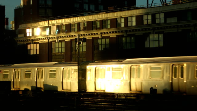 Cinematic Subway Train New York City Cinematic scene of a outdoor subway train passing through buildings in New York City during sunset. facade stock videos & royalty-free footage