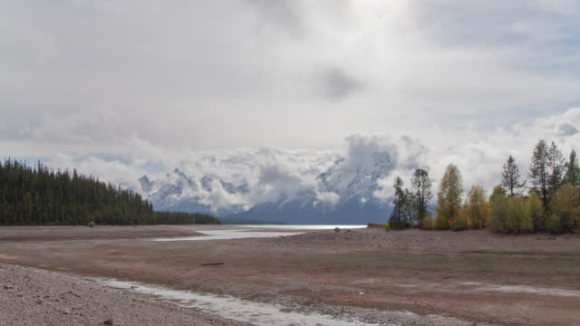 Cinematic Time-lapse of Clouds Swirling Over Grand Tetons with Foreground Stream video