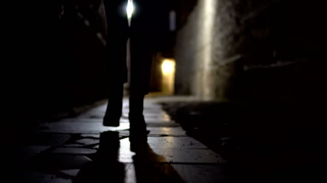 Cinematic treking of woman feet in boot walking on stone pavement in old alley dark street Cinematic treking of woman feet in boot walking on stone pavement in old alley dark street alley stock videos & royalty-free footage