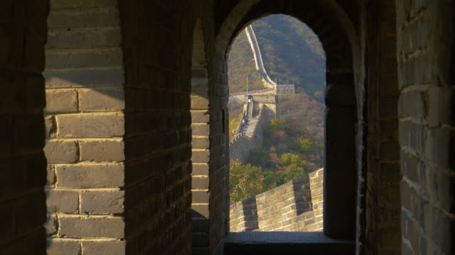 CLOSE UP: Cinematic view of a stone arched doorway offering a view of Great Wall