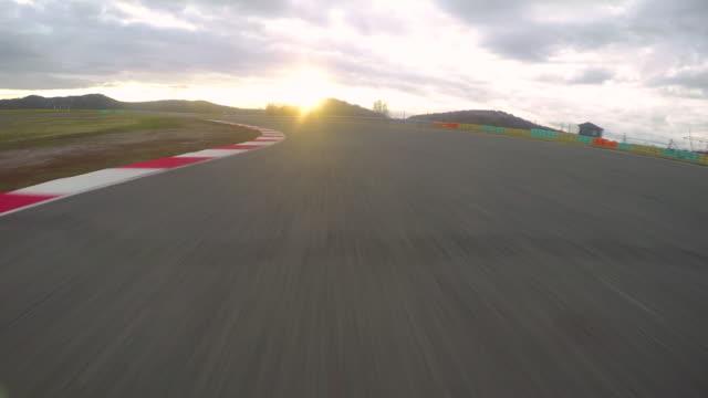 pov: güneş doğarken boş bir kablo kanalı aşağı hızlı bir araba sürüş sinematik görünümü. - pist stok videoları ve detay görüntü çekimi