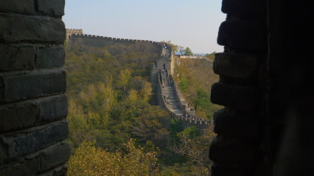 CLOSE UP: Cinematic view of tourists exploring the historic Great Wall of China.