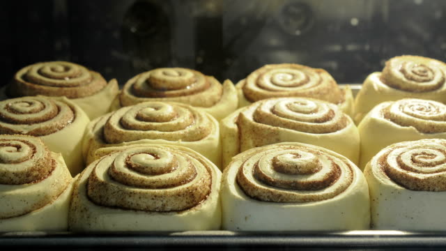 Cinnamon rolls buns baking in the oven time lapse Cinnamon rolls baking in the oven time lapse indulgence stock videos & royalty-free footage