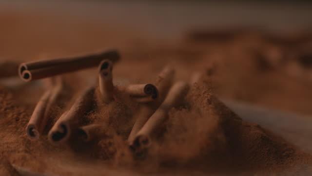 zimtstangen in gepulvertem zimt fallen - gemahlen stock-videos und b-roll-filmmaterial
