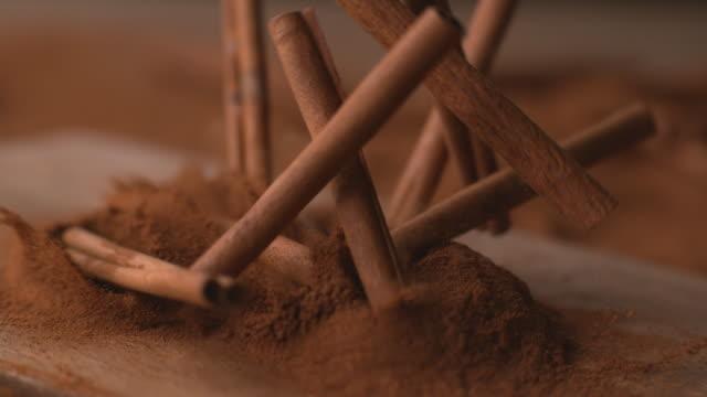 cinnamon sticks falling into powdered cinnamon - tavolo legno video stock e b–roll