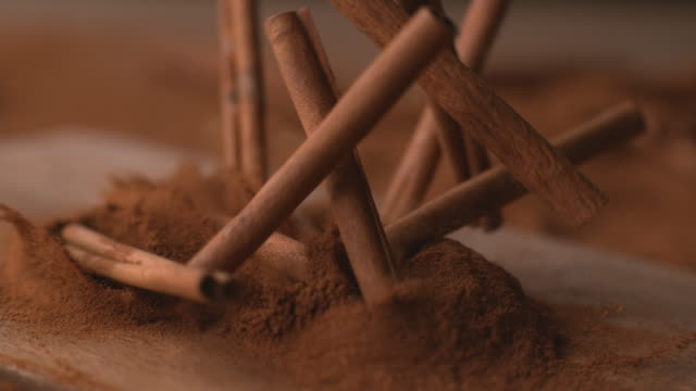 Cinnamon sticks falling into powdered cinnamon video