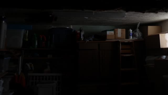 vídeos de stock e filmes b-roll de pittsburgh, pa - circa february 22, 2020 - a cluttered dark garage in residential home - house garage