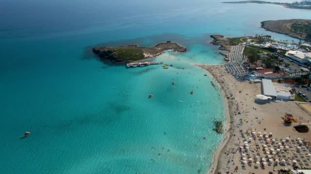 cirkling runt ayia napa kust full av hotell och pooler på en solig dag - turkos blå bildbanksvideor och videomaterial från bakom kulisserna