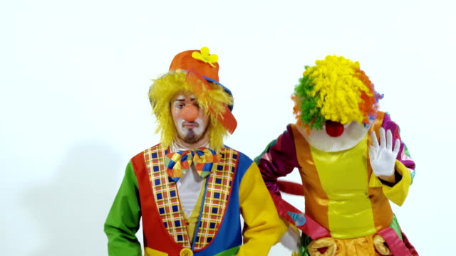 Circus clown trying to comb the other is hair and finally taking big scissors video