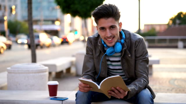 City boy reading a book on a bench video