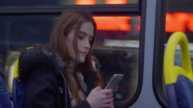 City bus at dusk, smartphone woman. 30 second plus clip of a young woman using her smartphone travelling on a bus in the city at night. The background blurs past as she speeds past the lights. She occasionally looks up and watches the city pass by. bus stock videos & royalty-free footage