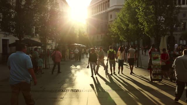city center of madrid: people walking and enjoying warm sunset - spain solar bildbanksvideor och videomaterial från bakom kulisserna