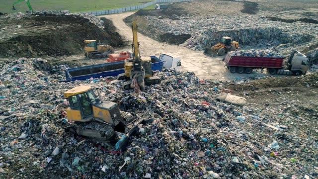 vídeos de stock e filmes b-roll de city dump. the bulldozer moves along the landfill, leveling the garbage. aerial view - economia circular