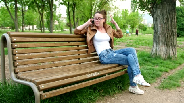 City girl sitting on a bench in the park and talking on her smart phone video
