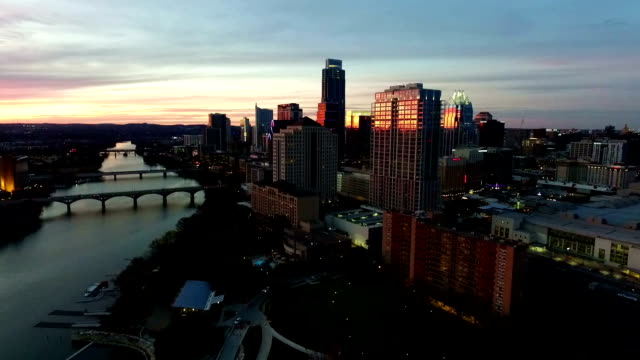 City lights turn on As the Sun Sets and Austin night life comes to life Aerial View Capital City of Texas Skyline Cityscape video